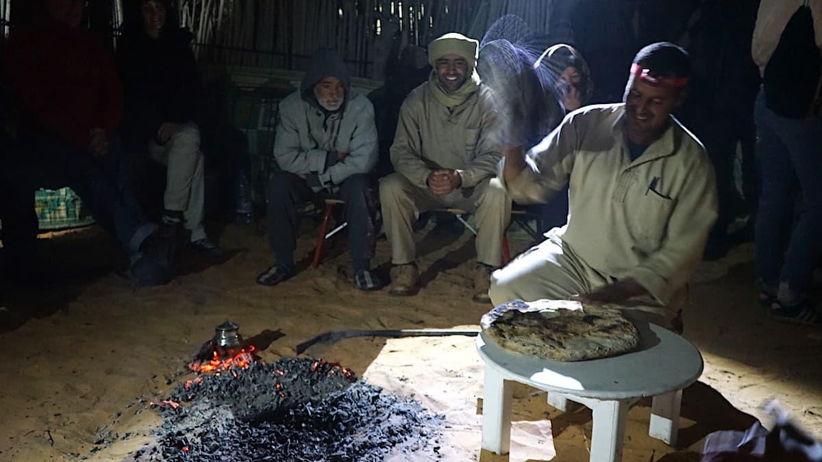 Essen in Tunesien: Mit dem Handtuch klopft der Koch Sand und Asche vom Brot ab.