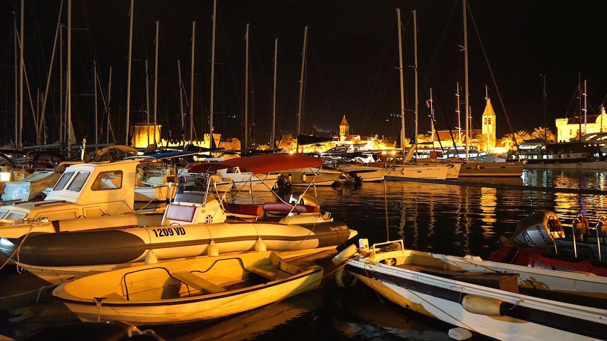 Blick über den Hafen auf die beleuchtete Altstadt Trogirs – Foto: Beate Ziehres