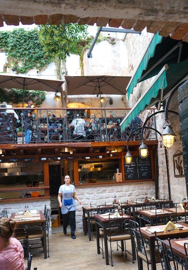 Blick in ein Restaurant in Trogirs Gassen – die meisten Gäste sitzen unter freiem Himmel. – Foto: Beate Ziehres