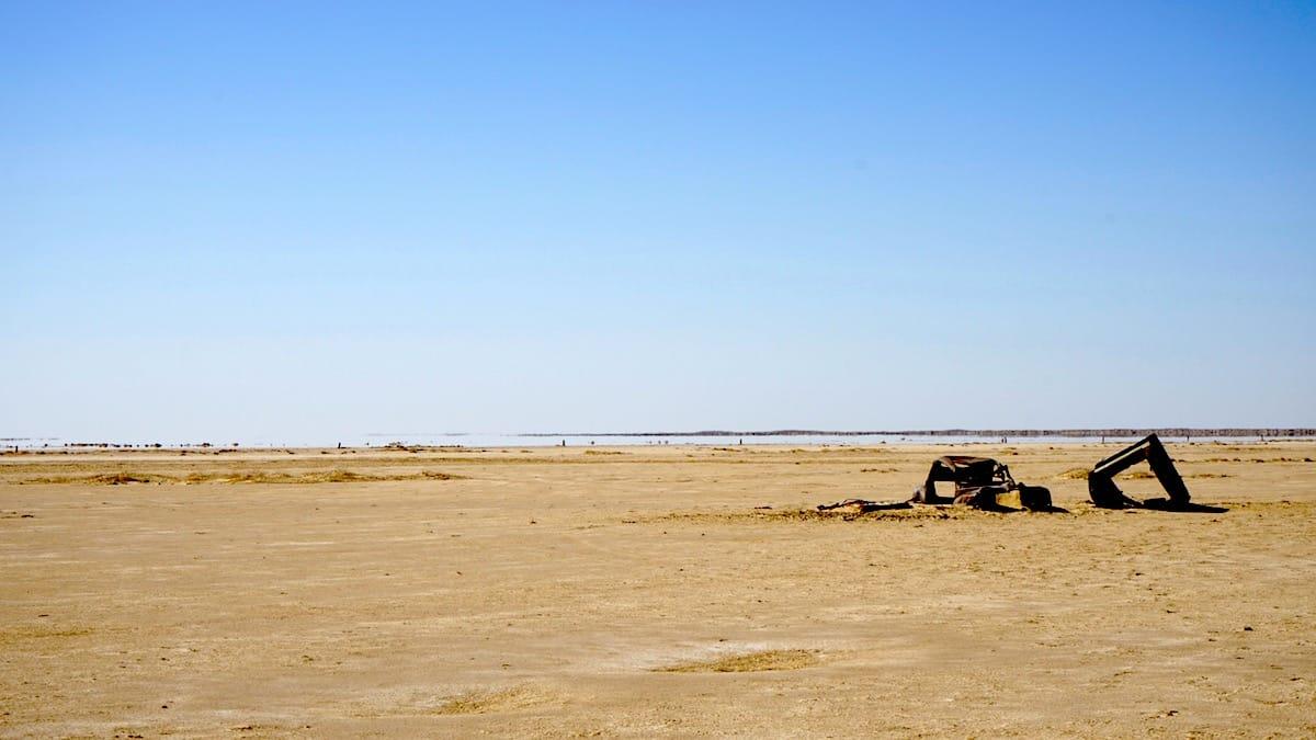 Tunesien, Star Wars Drehorte: Fata Morgana (hinter dem reellen Autowrack) am Rande des Chott el Jerid.