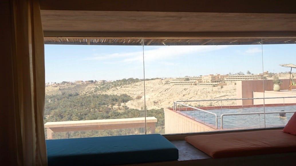 Tunesien Urlaub – Blick durch die Panoramascheibe eines Zimmers im Hotel Dar Hi, Nefta, Tunesien, auf den Thermalwasser-Pool. Foto: Beate Ziehres