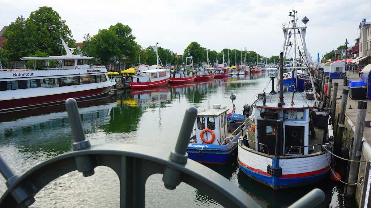 Blick in der Fischereihafen von Warnemünde. Im Vordergrund ein Teil der Drehmechanik der Bahnhofsbrücke – Foto: Beate Ziehres